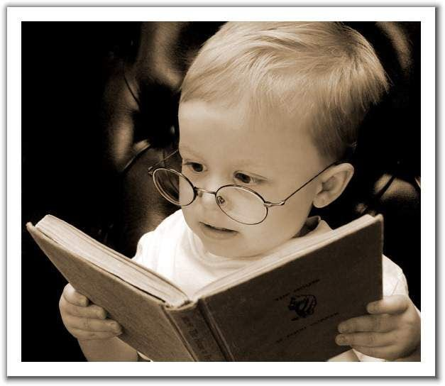 little boy reading with glasses on.