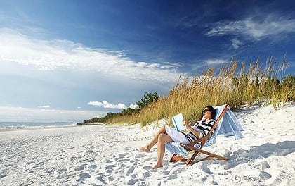 Relaxed Woman Reading Book On Beach